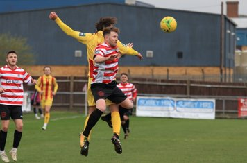 Enfield's Sam Youngs (yellow) challenges Tom Bird