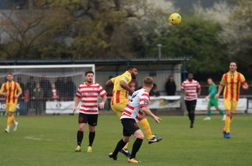 Enfield's Kezie Ibe (yellow) challenges Tom Bird