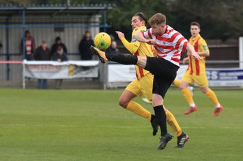 Kingstonian's Tom Bird (R) clears from Sam Youngs