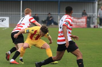 Kingstonian's Alfie Egan (L) and Jonathan Muleba and Enfield's Jay Porter