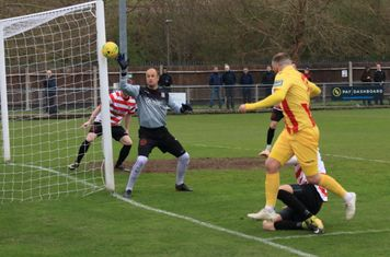 Enfield's Billy Bricknell (yellow) sees his shot deflected onto the post
