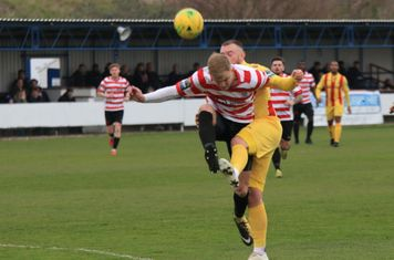 Kingstonian's James Richmond (L) clears from Billy Bricknell