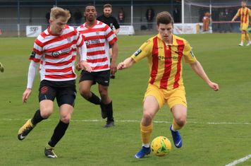Kingstonian's James Richmond (L) and Jonathan Muleba and Enfield's Josh Davison