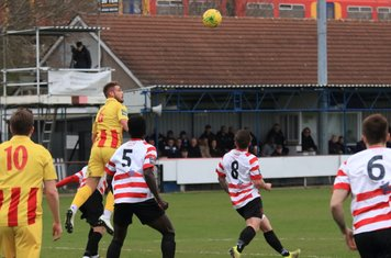 Enfield's Dan Rumens (yellow) wins a header