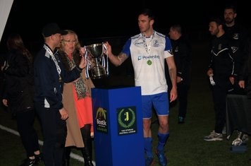 Injured captain Ryan Blackman (L) and stand-in Matt Johnson collect the trophy