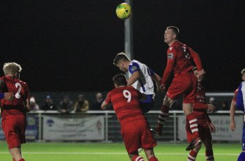 Hornchurch's Jordan Clark (red) heads clear from Dan Rumens
