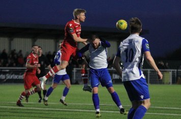 Hornchurch's Alex Bentley (red) wins a header against Billy Bricknell