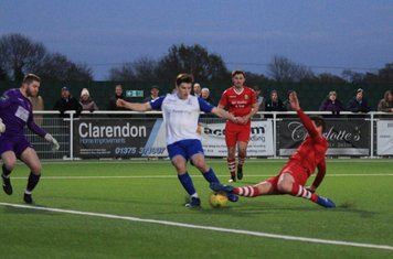 Hornchurch's Glenn Wilson (red) puts enough pressure on Jposh Davison to prevent him getting a clear shot.