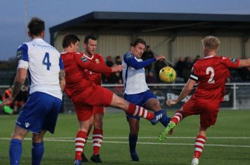 Enfield's Sam Youngs tries to curl a shot under pressure from Alex Bentley (2), Glenn Wilson (blue boots) and Kenzer Lee