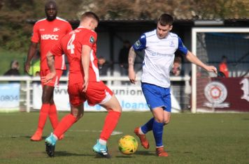 Carshalton's Luke Read (4) and Peter Adeniyi and Enfield's Sam Chaney
