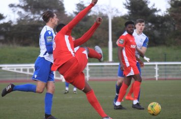 Carshalton's Daniel Pappoe (red) clears from Sam Youngs