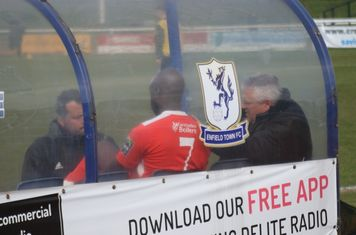 Carshalton player/manager Peter Adeniyi (red) discusses the first half with his coaching team before returning to the dressing. Whatever they decided clearly worked as two quick second-half goals put the match beyond doubt.