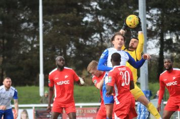 Carshalton keeper Billy Bishop catches under pressure from Sam Youngs
