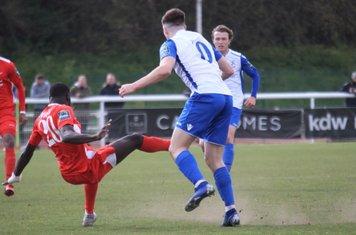 Carshalton's Jacob Mendy (20) clears from Josh Davison