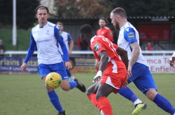 Enfield's Sam Youngs (L) and Billy Bricknell and Carshalton's Jacob Mendy