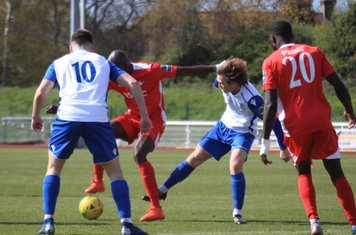Carshalton's Peter Adeniyi (red, L) holds off Mickey Parcell