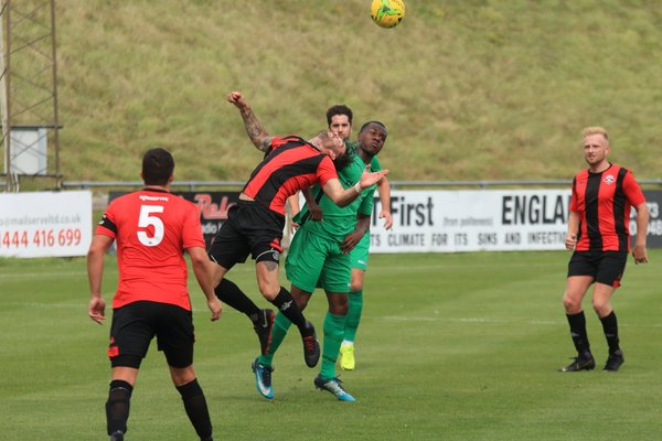 Lewes' Stacey Freeman heads clear from Ken Charles (green)