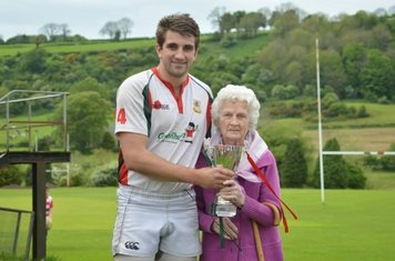 Johnny Cole from the Under 25s is presented the Gerry McCullagh memorial trophy by Mrs McCullagh. Photo by Bill Guiller.