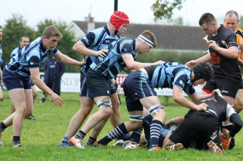 The Ballymoney forwards control the ruck ball.