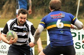 Simon takes on the Lisburn wing forward.
