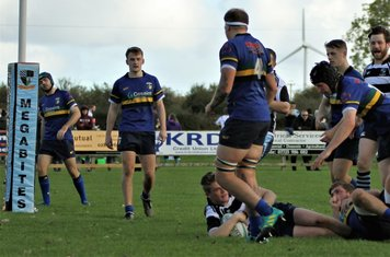 Scrumhalf,Matthew Steele, scores beside the posts.