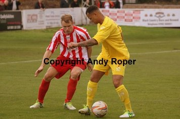 The Banbury player takes measures to keep the ball.....