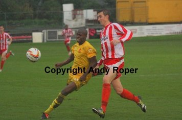 Aaron battles with Banbury striker Talabi.....