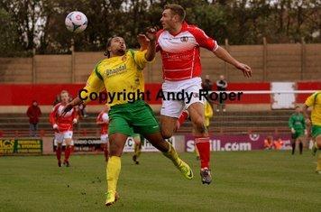 Luke challenges for the ball alongside home skipper Kyle May.