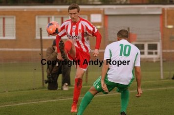 Aaron chips the ball over Town forward Callum Lewis.....