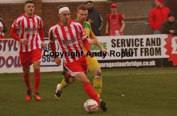 Ben wins the ball from North Ferriby 's Jamie Yates.....
