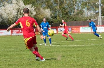 Samuel Nunn plays the ball forward for Gareth Heath