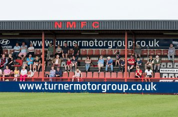 The spectators in the main stand watch...