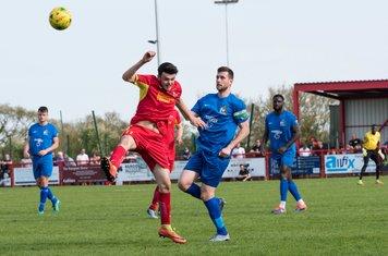 Mark McLeod heads clear as Ryan Gibbs challenges