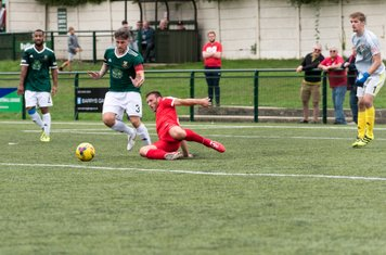 ...somehow manages to get a toe on the ball after Danny Boness blocks the shot...