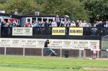 The Hornchurch fans behind the goal enjoy a pint with the game