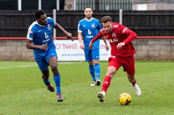 Former Borough player Bajram Pashaj brings the ball out of defence as a Borough attack breaks down