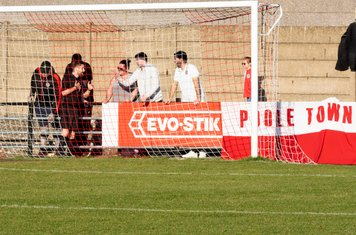 The Referee has to speak to some Poole Town supporters behind the goal