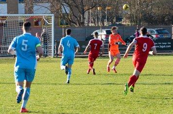 Luke Cairney heads clear...