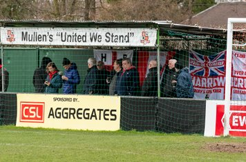 Borough supporters shelter behind the goal